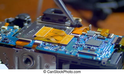 Radio Engineer Repairing Electronic Circuit Board with SMD...