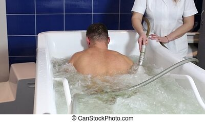 man passes procedure hydromassage - The young man is the...