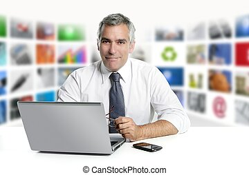 gray hair tv news screen presenter laptop smiling white desk