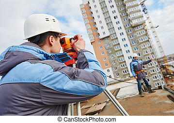 Two surveyors worker with theodolite - Two builders workers...