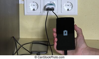 female hand holding smart phone plugged with wall charger....