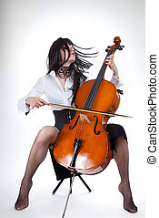Sensual girl playing cello and moving her hair, studio shot