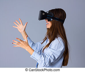 Woman using VR glasses - Young charming woman in blue shirt...