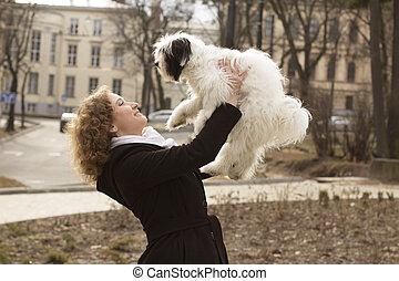 Young blonde woman playing with dog  in the park