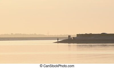 Anglers at dawn with fishing rods - Three standing anglers...