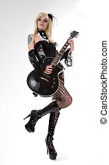 Sexy girl with guitar, focus on guitar and boots