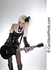 Sexy gothic girl playing guitar, studio shot over white...