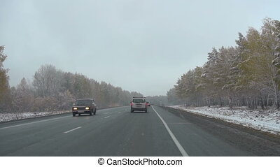 Early snow in October in Siberia, commuter highway - Cars on...