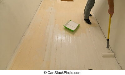 floor painting timelapse. Man paints the floor with white...