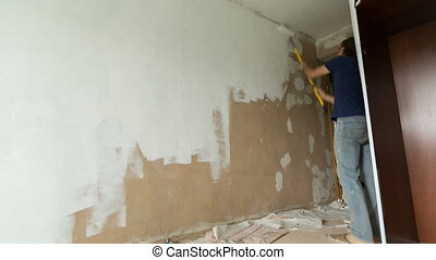 Painting walls timelapse. Man paints a wall in white color