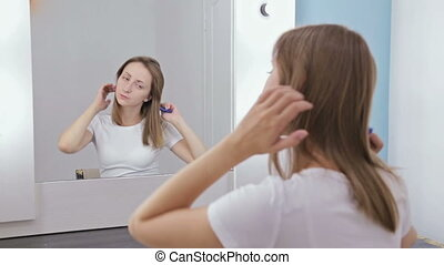 Young pretty woman combing her hair in front of the mirror....