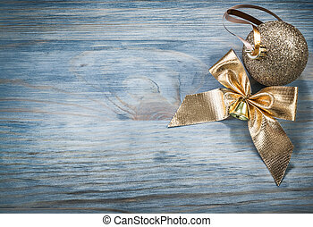 Goldish shiny Christmas ball bow on wooden board copy space...