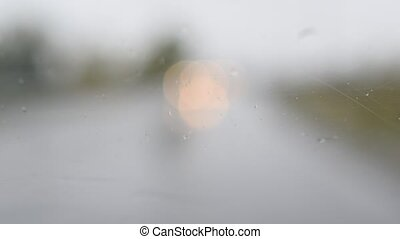 Driving in rain. Water drops on windshield - Driving in...