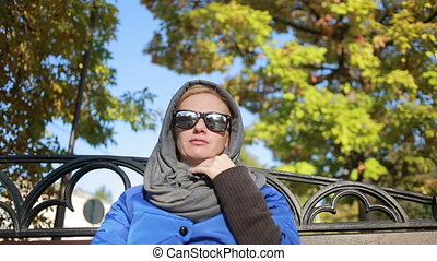 beautiful woman in sunglasses sitting on the bench in autumn...