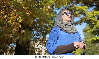 beautiful woman in sunglasses in autumn park. Keeps hands...