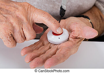 Senior Woman Pressing Alarm Button - Close-up Of Senior...