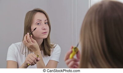 Beautiful young woman putting mascara in front of mirror