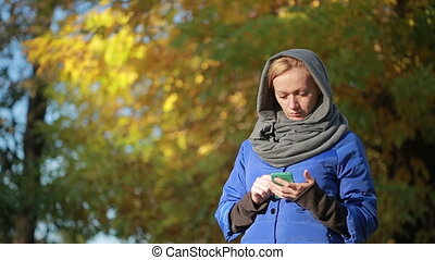 Young smiling woman talking on cell phone in the autumn...