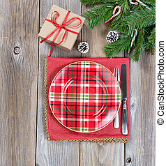 Xmas dinner setting with evergreen branches and gift box on rustic wooden boards