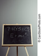 Physics word and formula E=mc2 on chalkboard - Handwritten...