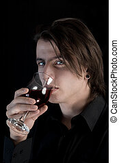 Handsome pale vampire with blue eyes drinking wine or blood,...