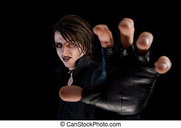Gothic boy with artistic make-up stretching his hand -...