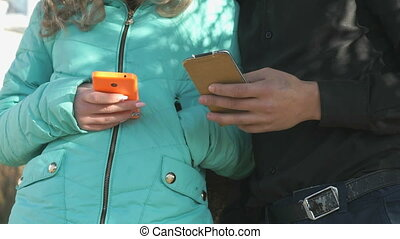 Girl and boy stand and hold the smartphones