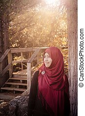 A pregnant muslim woman with natural background during...