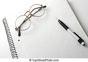calculating expenses - glasses and pencil on an open...