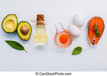 Selection food sources of omega 3 . Super food high omega 3 and unsaturated fats for healthy food. Halve avocado ,extra virgin olive oils ,white eggs and salmon fillets on white wooden background.