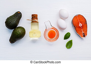 Selection food sources of omega 3 . Super food high omega 3 and unsaturated fats for healthy food. Avocadoes ,extra virgin olive oils ,white eggs and salmon fillets on white wooden background.