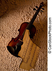 Old violin with burnt music sheet over grungy wall