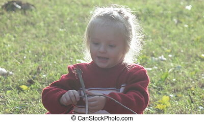 Girl child playing with branches - Refugee girl plays in the...