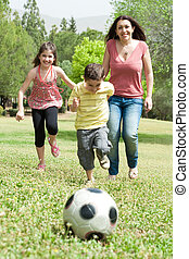 Family playing soccer and having fun, outdoor at the park
