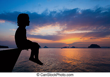 happy little boy sitting on beach at the dawn time. Concept...
