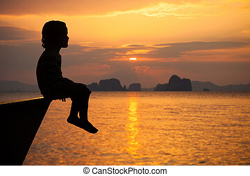 happy little boy sitting on beach at the dawn time Concept...