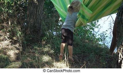 Smearing girl in hammock - Little girl with dirty feet and...