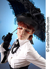 Beautiful girl in Victorian style clothes with umbrella,...