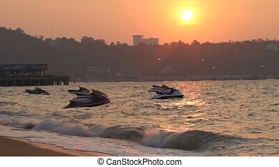 Jet skis swing on the waves. sunset in Pattaya, Thailand.