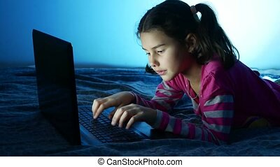 Teen girl working at laptop, the Internet play in the online...