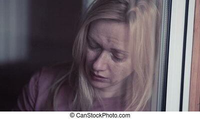 Sad girl near window. plachet woman.