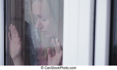 Sad girl near window. woman. tears