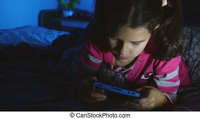 teen kid girl playing a portable video game console at night...