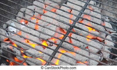 flaming charcoal briquettes on barbecue kettle grill
