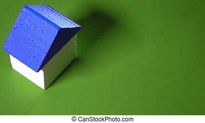 Female realtor placing toy house with blue roof and small...
