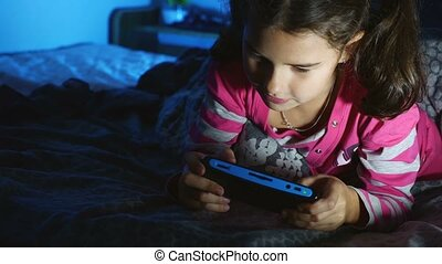 teen girl kid playing a portable video game console at night...