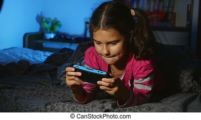 teen playing girl portable video game a console kid at night...