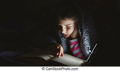 teen girl child reads book reading night with flashlight...
