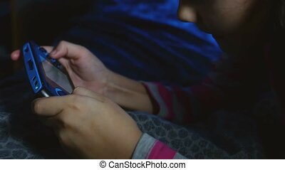 teen girl playing portable video kid online game a console...