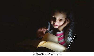teen girl child reads book reading at night with flashlight...